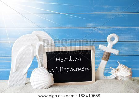 Chalkboard With German Text Herzlich Willkommen Means Welcome. Blue Wooden Background. Sunny Summer Card With Holiday Greetings. Beach Vacation Symbolized By Sand, Flip Flops, Anchor And Shell.