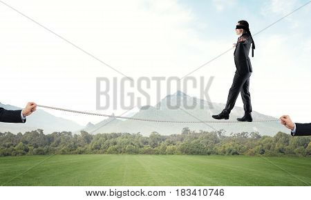 Businessman with blindfold on eyes walking on rope over natural background