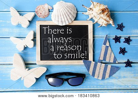 Flat Lay Of Chalkboard On Blue Wooden Background. Nautical Summer Decoration As Holiday Greeting Card. English Quote There Is Always A Reason To Smile