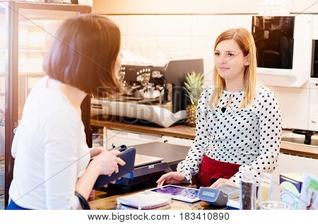 Woman paying with cash for coffee in cafe