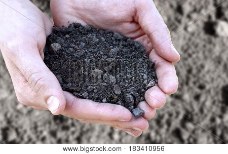 Concept Of Fertility And Ecology. Close Up Of Hands Holding Black Soil Over Black Ground