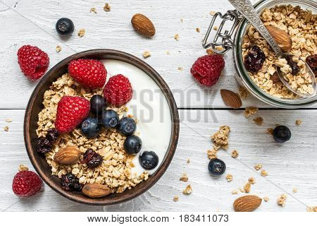 bowl of oat granola with yogurt fresh raspberries blueberries and nuts with jar of oats with a spoon on white wooden board for healthy breakfast. top view