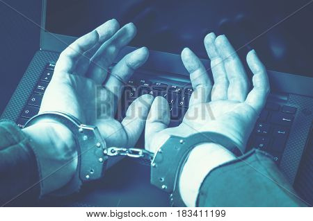 Blue matt toning image of arrested hacker with hands in handcuffs on the laptop keyboard. Cyber crime concept. Focus on hands.