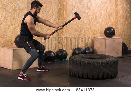 Sport Fitness Man Hitting Wheel Tire With Hammer Sledge Crossfit Training, Young Healthy Guy Gym Interior