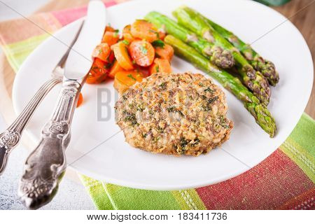 Meat rissole with glazed carrots, asparagus on the plate