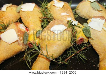 chicken legs brews in a baking pan with sage and rosemary