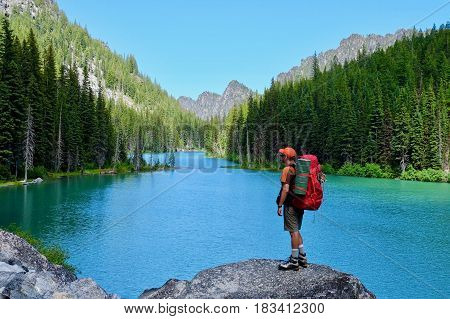 Man hiker on rocks by alpine lake. Nada lake. The Enchantments. Leavenworth. Seattle. Washington State. USA.
