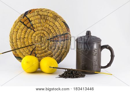 Two lemons mug tea stand and aromatic sticks isolated on white background.
