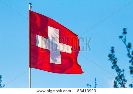 Swiss Confederation (Switzerland) national flag waving on blue sky background.