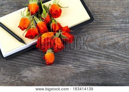 red rose on a notebook and pencil on a white background. good for holidays valentines's gift. Copy space for text.