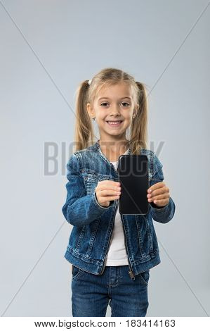 Little Teenage Girl Shows Cell Smart Phone Screen With Empty Copy Space, Isolated Over Gray Background