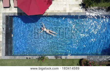The young beautiful woman swims in the pool flat lay.