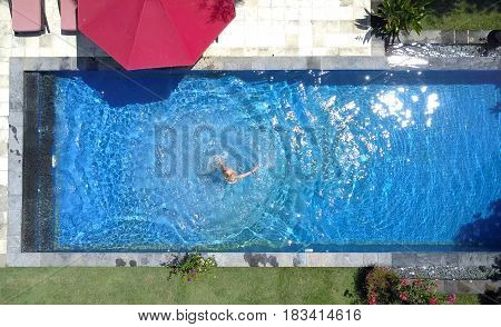 The young beautiful woman in the pool flat layview from drone .