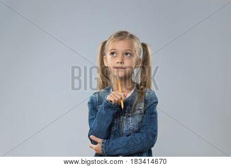 Little Teenage Girl In Jeans Coat, Small Kid Looking Up To Copy Space Think Hold Chin Isolated Over Gray Background