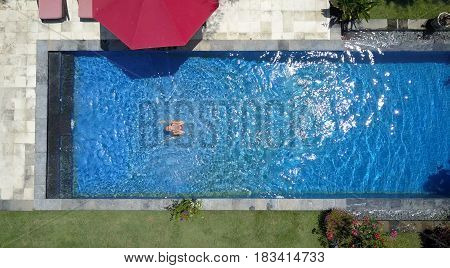 The young beautiful woman in the pool flat lay dron view.