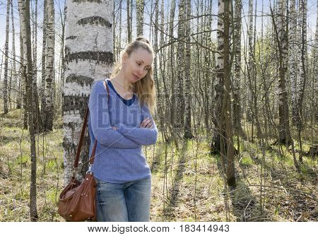 The young woman near a birch in park in the early spring