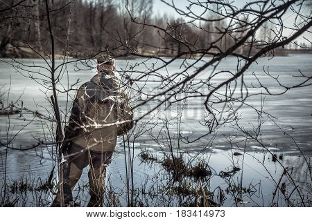 Hunter man with shotgun standing in thickets at river covered with ice during spring hunting season