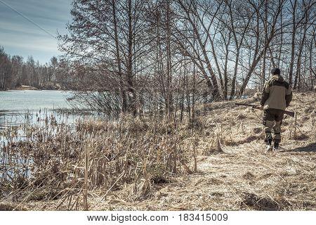Hunter man walking along river bank during spring hunting season