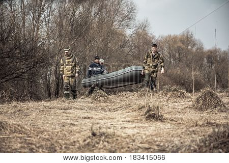 Group of men in camouflage with rubber boat crossing dry rural field with bushes on background during spring hunting