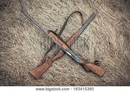 Crossed hunting guns on dry grass on haystack as hunting background