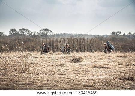 Group of hunters hiding in rural field with dry grass during hunting season in overcast day