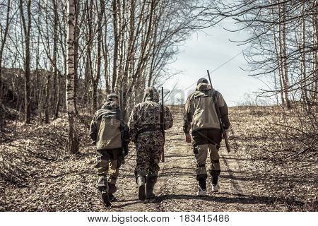 Group of men hunters going up on rural road during hunting season