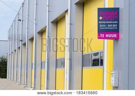 ALMELO NETHERLANDS - JULY 9 2016: For Rent (Te Huur) sign in front of a commercial warehouse with yellow roller doors