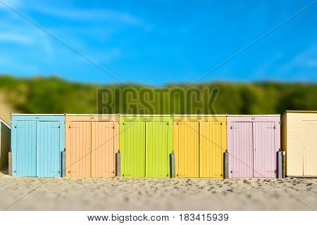On the Beach by the Sea - beautiful colorful beach huts on a sandy beach on a sunny day - miniature effect