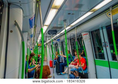 MADRID, SPAIN - 8 AUGUST, 2015: Inside subway train wagon leaving from Barajas Airport station with some people sitting around.