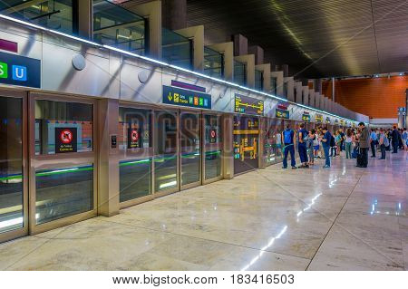 MADRID, SPAIN - 8 AUGUST, 2015: Train station connection hall to Barajas Airport gates with dorrs, info screens and signs arounf.