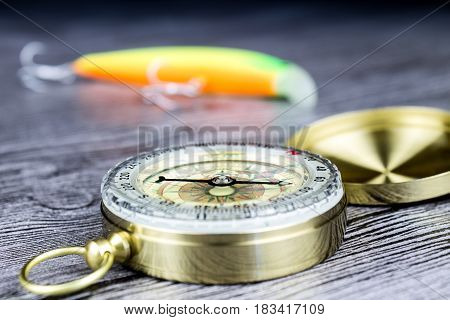 fishing tackles with compass on the wooden table