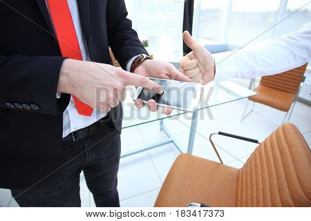 Close up of a man using mobile smart phone, blank black screen near big glass windows at office