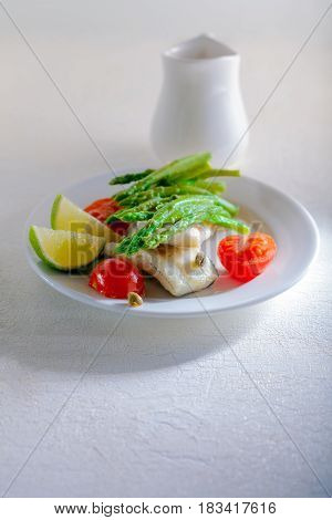 Mackerel fillets with asparagus on a white surface