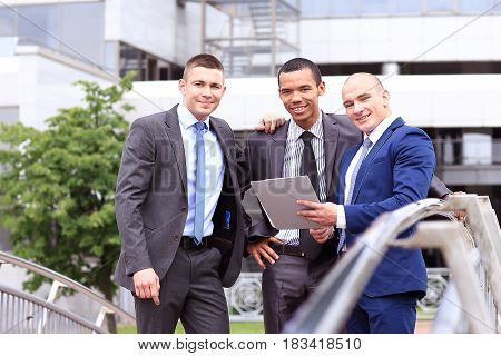 Three Businessmen Discussing Document Outside them Office