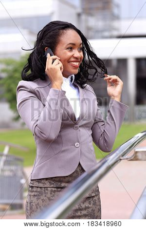 happy young businesswoman talking on cell phone outdoors