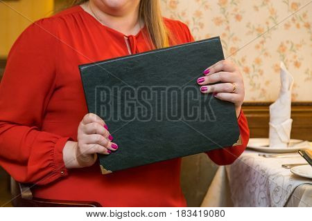 Woman in a red dress holding a menu in hand close up