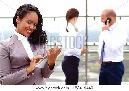 Conversation with the client. African businesswoman businessman holding a tablet in hand standing outdoor