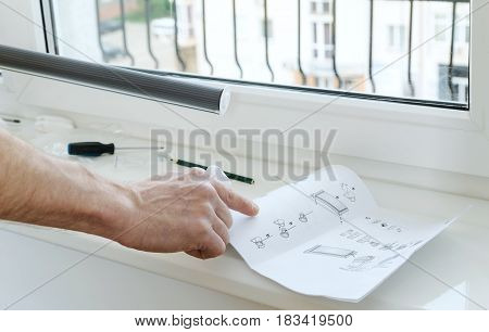 Forefinger of a man's hand directed to instruction for installing roller blind.