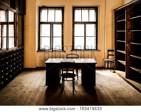 Retro style office room with wooden table, old chairs and cabinets. Vintage theme.