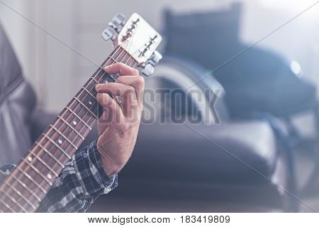 Telling you my story. Inspired artistic talented handicap sitting on the couch next to the wheelchair indoors and meditating while playing the guitar