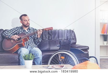 My musical treatment. Inspired skilled young disabled sitting on the sofa next to the wheelchair indoors and meditating while playing the guitar
