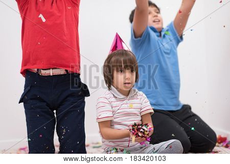 Happy kids celebrating party with blowing confetti
