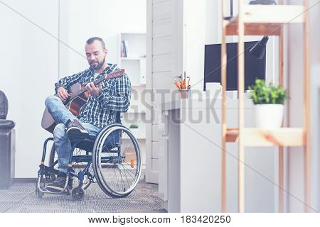 Distracting from all problems. Gifted capable young disabled sitting on the wheelchair indoors and enjoying free time while playing the guitar