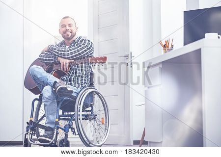 Sharing happiness with you. Smiling charming young disabled sitting on the wheelchair indoors and enjoying free time while learning playing the guitar