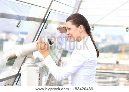 Caucasian woman looking through binoculars over the city