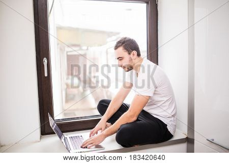 Happy Smiling Man Sitting On Windowsill And Typing On Laptop At Home