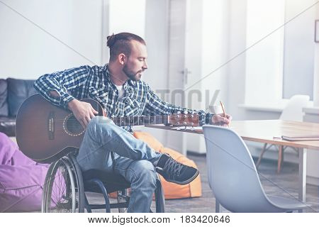 Motivating other for positivity. Skilled talented young invalid sitting on the wheelchair indoors and enjoying free time while playing the guitar and writing song