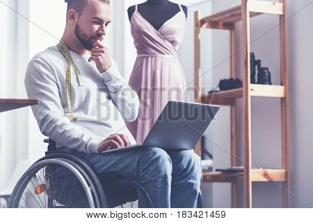 Working on my new collection. Involved positive disabled designer sitting on the wheelchair in the studio and working while using gadget and tape measure