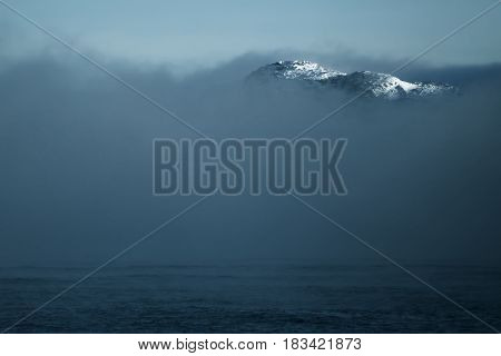 Mountain peak from clouds at Arctic Ocean