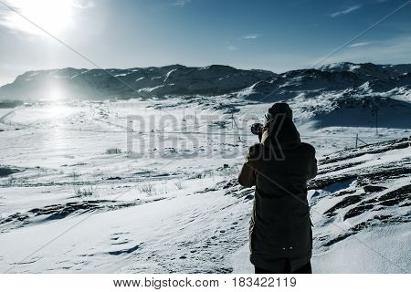 Man Photographer With Camera At Winter Mountain